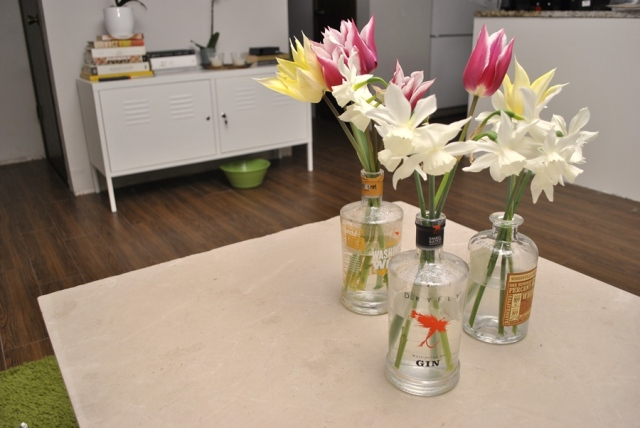 Tulips and daffodils in liquor bottles on marble coffee table