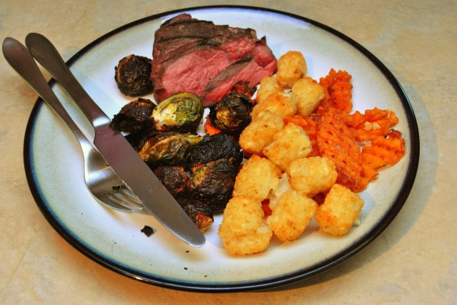 perfect medium rare sous vide steak with tots and burned brussels sprouts